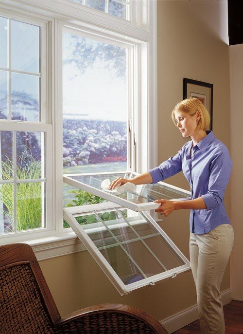Woman effortlessly cleaning interior of double hung window