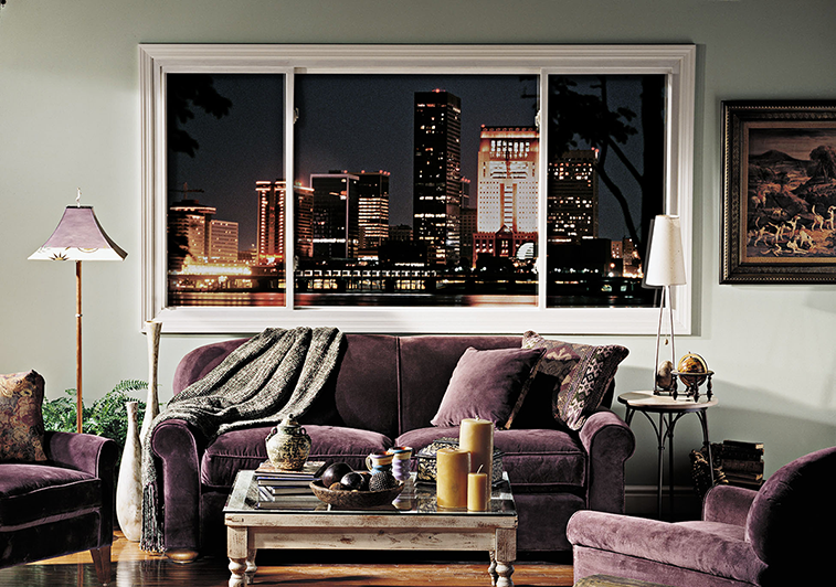 Interior of living room featuring horizontal sliding windows with a view of a nighttime city skyline windows
