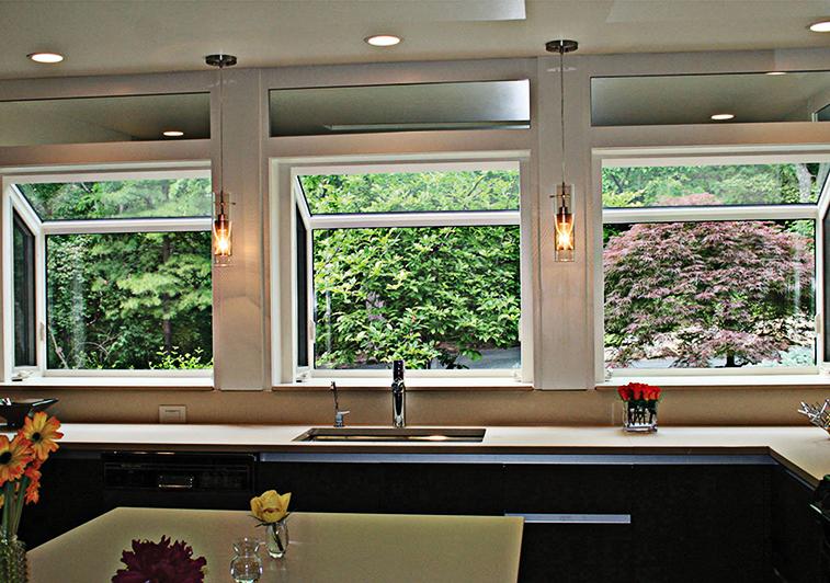 Interior of kitchen featuring three side-by-side garden windows overlooking foliage