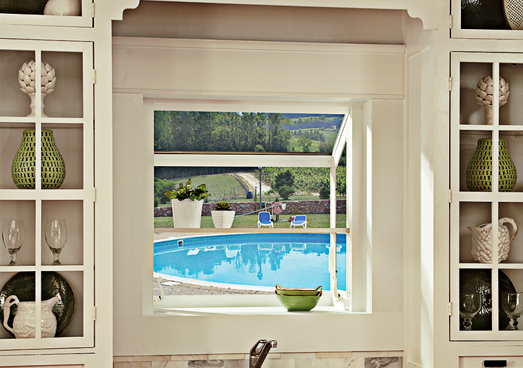 Interior kitchen scene featuring a garden window placed above the kitchen sink  which overlooks a backyard pool