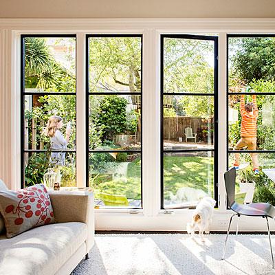Living room interior featuring dark-framed floor-to-ceiling casement windows