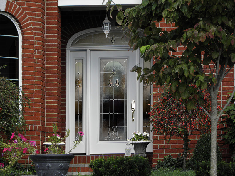 White exterior fiberglass door with stained glass window inlay and matching side lights and arched transom window